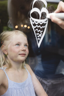 Portrait of little girl behind window pane watching her mother painting ice cream cone - MIDF000768