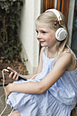 Smiling little girl listening music with headphones and smartphone - MIDF000771