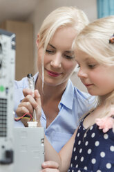 Mother and little daughter checking current flow of computer - MIDF000774