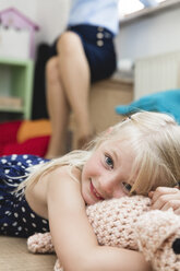 Portrait of little girl with cuddly toy lying on the floor while her mother sitting in the background - MIDF000777