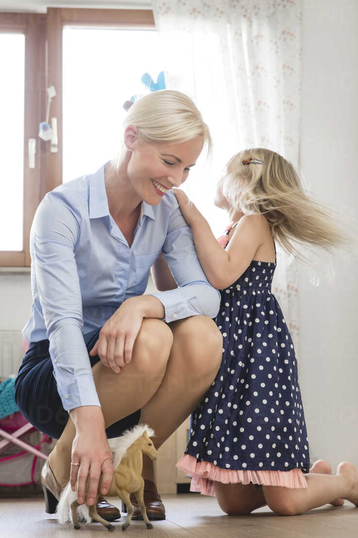Businesswoman playing with her little daughter at children's room - MIDF000780 - Miriam Dörr/Westend61