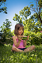 Little girl sitting on a meadow holding slice of watermelon - LVF005137