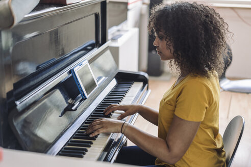 Young woman playing piano, reading notes from digital tablet - RIBF000427