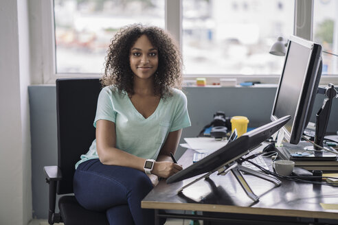 Young woman sitting in office with digital tablets, smiling - RIBF000445