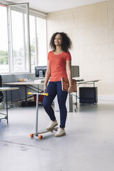 young woman carrying laptop, using kickboard in office - RIBF000457