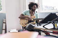 Young man playing guitar in office - RIBF000487
