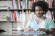 Young man working in library, using futuristic computer - RIBF000532