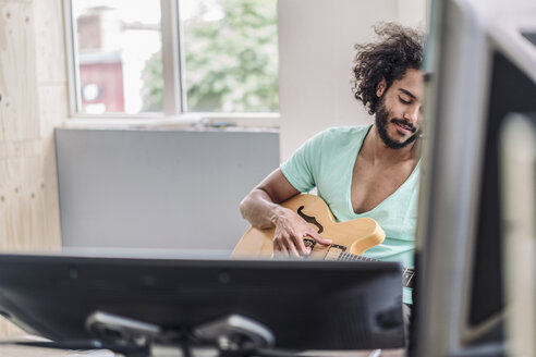 Young man playing guitar in office - RIBF000553