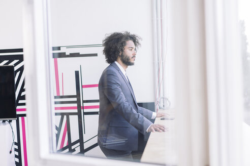 Young businessman standing by window, thinking - RIBF000565