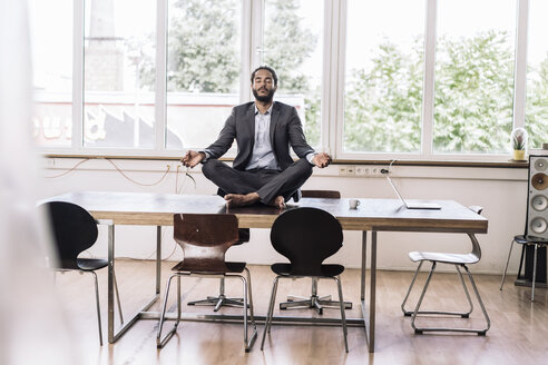 Young businessman sitting cross-legged on desk in office - RIBF000577