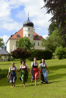 Germany, Bad Heilbrunn, four happy women wearing dirndls running hand in hand on a meadow - LBF001447
