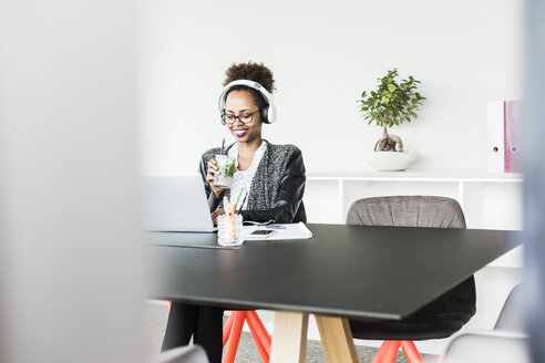 Businesswoman with headphones and beverage sitting at desk looking at laptop - UUF008230