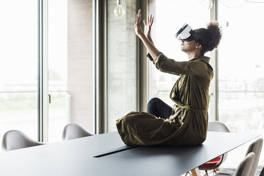 Woman in office sitting on conference table using virtual reality glasses - UUF008263