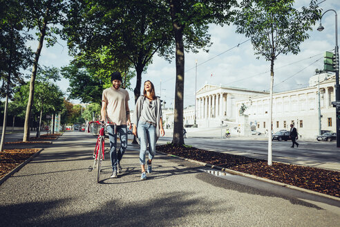 Austria, Vienna, young couple with bicycle in front of Parliament building - AIF000344