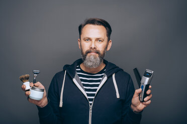 Portrait of smiling man holding accessories for shaving - IPF000308
