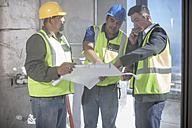 Architect and construction workers discussing construction plan - ZEF009171