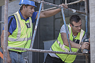 Two construction workers on scaffolding working on construction site - ZEF009189