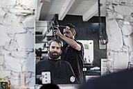 Barber blow-drying hair of a customer - ZEF009204