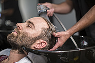 Customer laid back as he gets his hair washed - ZEF009228