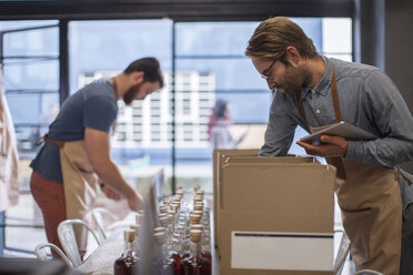 Two colleagues shipping liquor in a distillery - ZEF009237