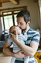 Father kissing baby boy at home - HAPF000654