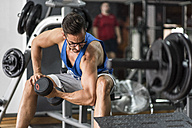 Man lifting dumbbell in gym - JASF000989
