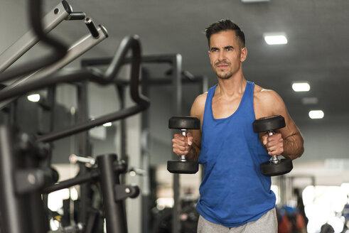 Man lifting dumbbells in gym - JASF000992