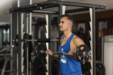 Man lifting barbell in gym - JASF000995