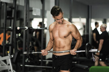 Man lifting barbell in gym - JASF000998
