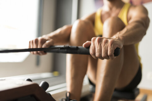 Man exercising at rowing machine in gym - JASF001001