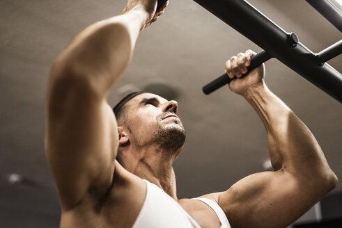 Man doing chin-ups in gym - JASF001004