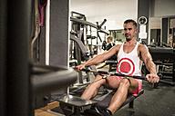 Man exercising at rowing machine in gym - JASF001007