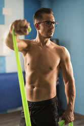 Man exercising with resistance band in gym - JASF001010