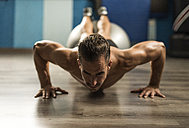Man doing push-ups with fitness ball in a gym - JASF001013