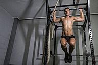 Man doing chin-ups at power rack - JASF001016