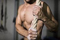 Athlete with chalk in hands holding rope - JASF001019