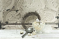 Quail eggs in a glassbowl, spoon and Easter wreath - ASF005953