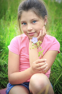 Portrait of smiling girl with flower sitting on a meadow - VTF000540