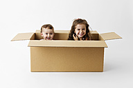 Two happy little children together in a cardboard box - LITF000391
