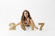 Portrait of smiling little girl playing with cardboard numbers forming the date '2017' - LITF000400