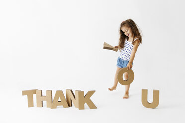 Smiling girl forming the word 'Thank You' with cardboard letters - LITF000403