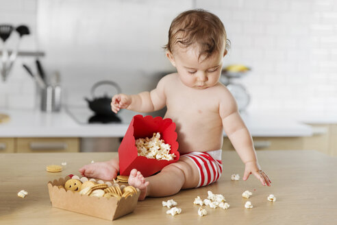 Baby boy sitting on kitchen worktop playing with popcorn - LITF000409