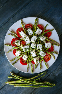 Plate of green asparagus, tomato slices and diced sheep cheese on  wood - KIJF000603