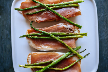 Bread slices with cured ham and grilled green asparagus on platter - KIJF000609