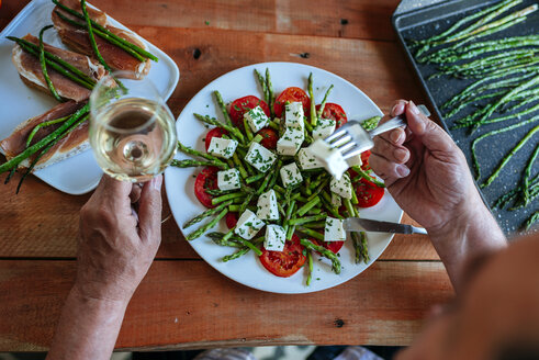 Senior man eating salad of green asparagus, tomatoes and sheep cheese accompanied by white wine - KIJF000612