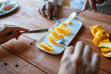 Hands of two persons eating orange slices with cutlery - KIJF000615