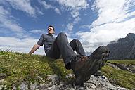 Austria, Tyrol, hiker sitting, hiking shoe - MKFF000303