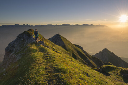 Austria, Tyrol, hiker on ridge at sunrise - MKFF000318