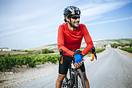 Spain, Andalusia, Jerez de la Frontera, Cyclist man while smiling - KIJF000621