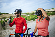 Spain, Andalusia, Jerez de la Frontera, couple of bikers drinking water on a rural road between vineyards - KIJF000624